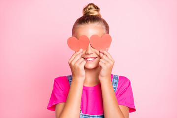 Close up photo of cheerful funky little girl hiding her eyes behind red heart shapes smiling...