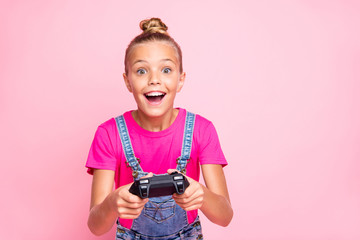 Photo of rejoicing cute nice schoolgirl excited about level complete playing video games wearing t-shirt jeans denim holding joystick with her hands isolated over pink pastel color background