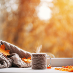 A Cup of hot autumn coffee or tea on the window . The concept of hygge. Hot drink in cold autumn...
