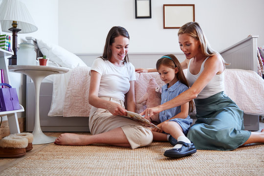 Same Sex Female Couple Sitting On Bedroom Floor Reading Book With Daughter At Home Together
