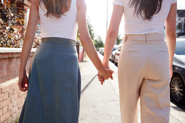 Close Up View Of Same Sex Female Couple Holding Hands As They Walk Along Road From Behind