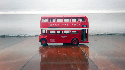 Poster London red bus toy bus on a wooden floor with a message