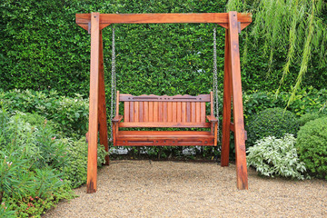 Wooden swing chair in natural green garden. Beautiful garden furniture.