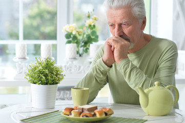 Portrait of elderly man drinking cup of coffee