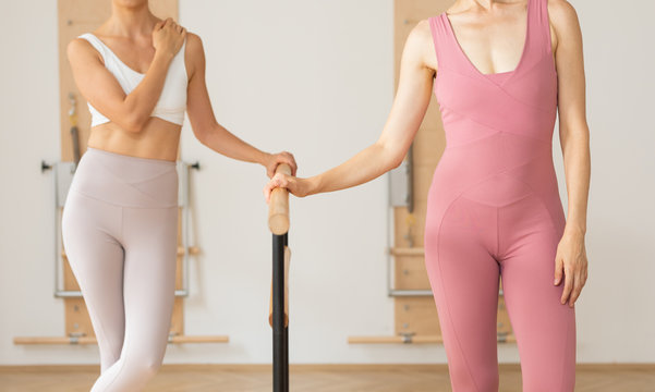 Two unrecognisable woman dancers standing next to barre at ballet studio.