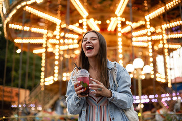 Outdoor portrait of joyful young pretty brunette female in casual clothes posing over amusement park with closed eyes and broad smile, holding cup of lemonade in hands