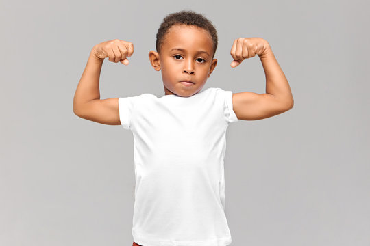 Picture of cute dark skinned little boy in white t-shirt tensing bicep, showing arm muscles, being proud of himself after physical training, looking at camera with confident facial expression