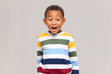 Genuine human facial expressions and feelings. Isolated image of funny cute Afro American boy in striped sweater opening mouth widely and raising eyebrows, being afraid of scary movie or dentist
