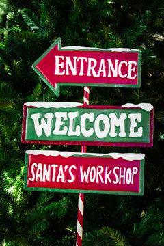 "North Pole directional sign saying ""Entrance, Welcome, Santa's Workshop"""