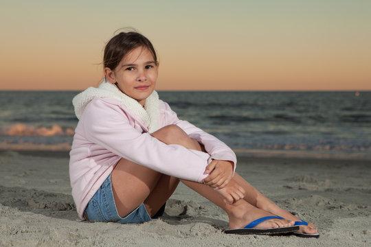 8 Year old girl sitting on beach at dusk