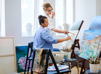 Creative painter and her protege working in a studio