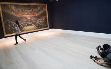 Sotheby's staff pose for a photograph with Banksy's 'Devolved Parliament' which has an estimated value of 1.5-2 million British pounds in a forthcoming sale in London