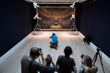 Members of the media take photos as a Sotheby's staff poses for a photograph with Banksy's 'Devolved Parliament' which has an estimated value of 1.5-2 million British pounds in a forthcoming sale in London