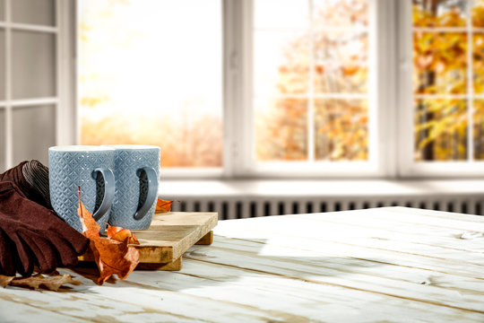 Autumn desk with mug and blurred fall window space