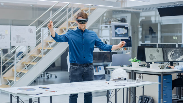 Engineering Software Developer Wearing Virtual Reality Headset Uses Gestures to Interact with Augmented Reality while Designing Industrial Engine Model in Modern Facility. AR Mock-up Concept