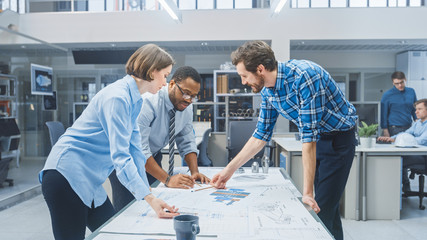 In the Industrial Engineering Facility: Female Designer Works with Industrial Engineer and Master Technician, They have Discussion, Analyse Engine Design Technical Drafts that are Lying on the Table