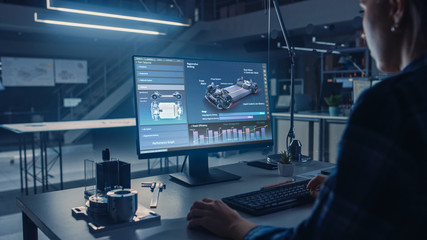Engineer Working on Desktop Computer, Screen Showing CAD Software with Car Efficiency and Engine Concept. Industrial Design Engineering Facility. Over the Shoulder Shot