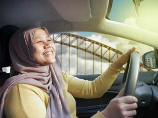 Smiling Muslim Lady Driving a Car