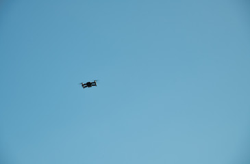 Black drone in the blue sky. Freedom concept