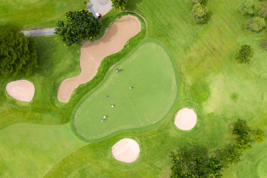 Aerial view of players on a green golf course. Golfer playing on putting green on a summer day. People lifestyle relaxing time in sport field or vacation outdoors activity.