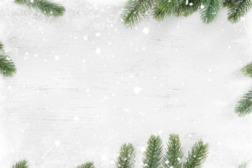 Pine leaves decorated as a frame on a white wooden background  with snowflakes. Merry Christmas and winter holiday background. Wall mural