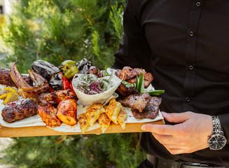 Man holding grilled kebab plate
