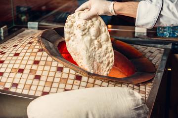 Men putting lavash pita flatbread into special oven tandoor