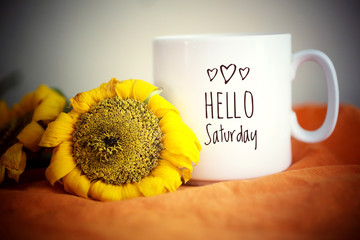 Hello Saturday greeting on a white mug of coffee. With sunflowers and orange colors background. Morning coffee concept.