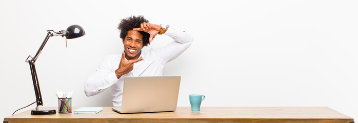 young black businessman feeling happy, friendly and positive, smiling and making a portrait or photo frame with hands on a desk