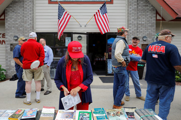 A woman wearing a hat supporting U.S. President Trump browses free books at the Chicken Burn in Milwaukee