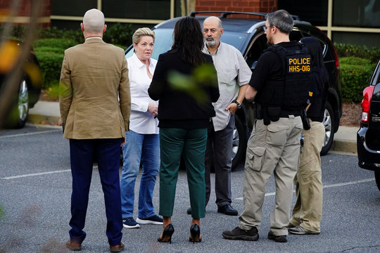 Federal agents speak with Victoria Nemerson, General Counsel for Alpha Medical Consulting, and an unidentified man, prior to executing a search warrant on multiple business at an office park in Lawrenceville