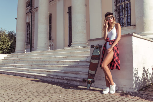 Girl in summer in city, calling on cell phone, free space for text. Skateboard, board for riding, resting listens to message bell. Tanned figure of beautiful woman in baseball cap and sunglasses.