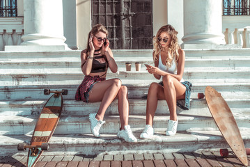 Two girls beautiful girlfriends summer city. They relax weekends, call mobile phone, write read message social networks, online app Internet, coffee tea. Tanned figures, sports fitness slim girls.