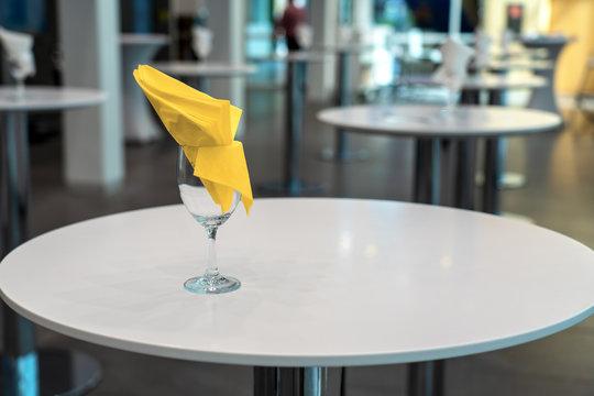 Stehtisch mit gelber Serviette im Foyer eines Kongresses