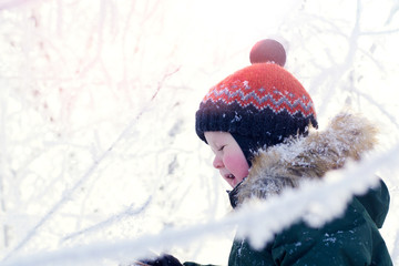 Portrait of a boy in a bright orange hat on the background of a winter Park