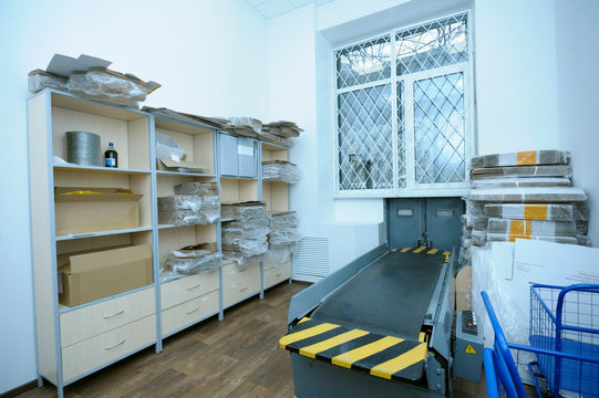 At the post office, view of the receipt and delivery room: belt conveyor, window and boxes with piles of letters and parcels