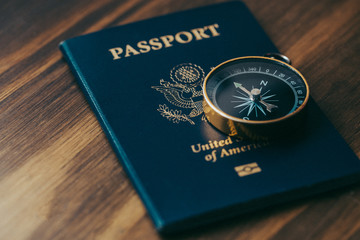 One gold compass on top of a blue American passport