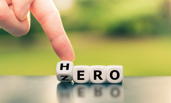 """From zero to hero concept. Hand turns a dice and changes the word """"zero"""" to """"hero""""."""