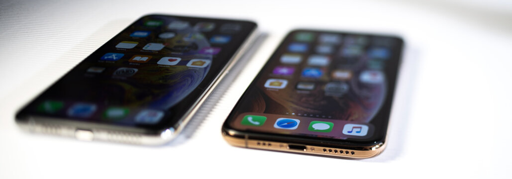 PARIS, FRANCE - SEP 27, 2018: Wide image comapring the new Apple Computers iPhone Xs and Xs Max with home apps on the gorgeous OLED display on stripe cardboard background