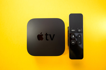 Paris, France - 25 Mar 2019: Directly above view of Apple TV 4k player with Siri remote control assistant Apple TV plus subscription film series documentaries - includes the logotype on the cover