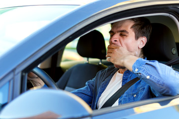 Man is yawning behind steering wheel of car. Sleepy driver is riding in automobile. Male is violating rules of road. Driving without rest concept. Deadly danger on route of modern city.