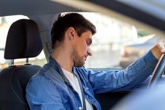 Man fell asleep behind steering wheel of car. Sleepy driver is riding in automobile. Male is violating rules of road. Driving without rest concept. Deadly danger on route of modern city.