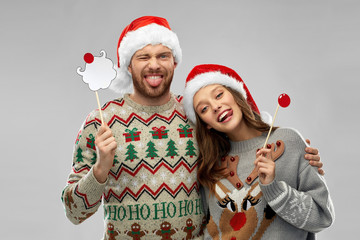 christmas, photo booth and holidays concept - happy couple in ugly sweaters posing with party props