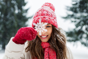 people, season and christmas concept - portrait of happy smiling teenage girl or young woman with snowflake in winter park