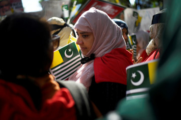 A woman holds a flag of Azad Kashmir at a protest in solidarity with the people of Kashmir