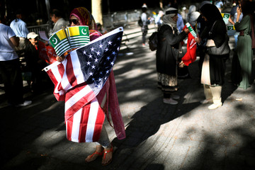 A woman carries the flag of Azad Kashmir and the American flag during a protest in solidarity with the people of Kashmir