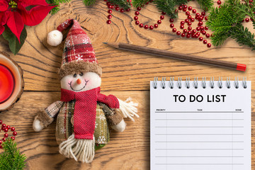 Snowman rag doll and to do list notepad on wooden background