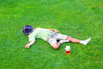 drunken bavarian men sleeps in the meadow