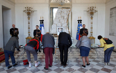 People sign the books of condolences to pay tribute to late former French President Jacques Chirac at the Elysee Palace in Paris