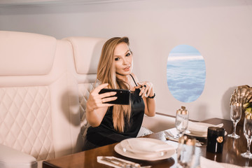 beautiful young girl in the cabin of a business class airplane with a phone in her hands comfortable luxury travel